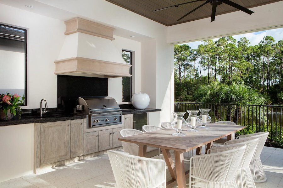 chairs dining table stove top outdoor kitchen in Florida trees